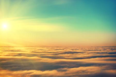 青空、夕焼けの太陽、雲の平面からの絶景 写真素材
