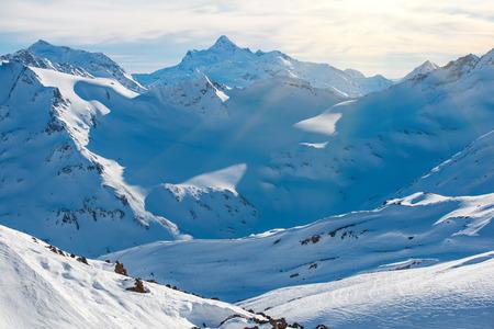 Besneeuwde blauwe bergen in de wolken. Winter skigebied Stockfoto