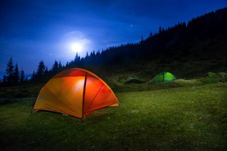 Two Illuminated orange and green camping tents under moon, stars at night