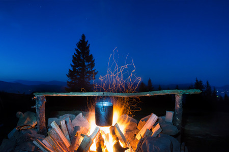 under fire: Cocinar los alimentos en la olla en el fuego bajo el cielo azul noche con muchas estrellas Foto de archivo