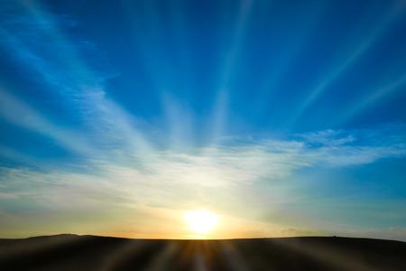 Zon stijgt boven het land op de blauwe hemel. Natuur achtergrond met zonnige stralen