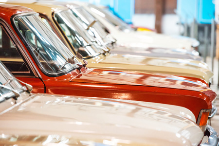 Red and white cars in a row on parking lot photo