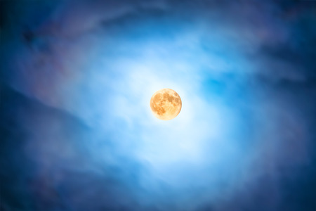 nebulous: Night view at the full moon through moving blue clouds. Abstract scene