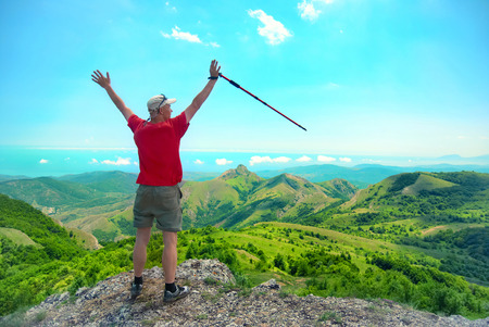 Young happy man with hiking stick standing on the rock with raised hands and looking to green landscape photo