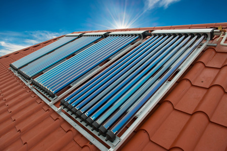 Vacuum collectors- solar water heating system on red roof of the house.