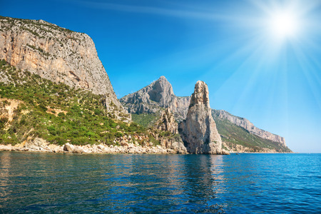 rock cliff: Coast and blue Mediterranean sea and bright sun on the sky in Sardinia, Italy. View from the yacht