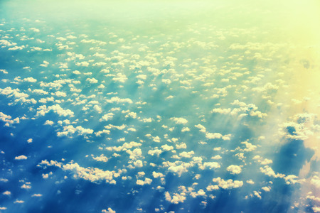 View from a plane to sunset on the sky with sunrays. Fluffy clouds background photo