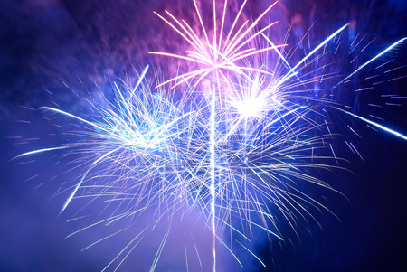 Blue and purple colorful fireworks on the black sky background. Holiday celebration. 스톡 콘텐츠