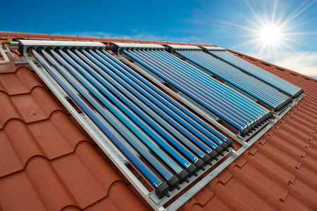 conservation: Vacuum collectors- solar water heating system on red roof of the house.