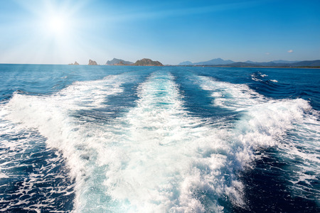 motor yacht: Waves on blue sea behind the speed boat water with bright sun shining on the sky Stock Photo