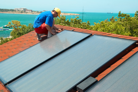 human energy: Worker solar water heating panels on the roof. Stock Photo