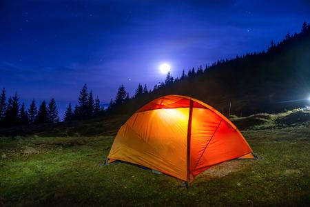 Verlicht oranje camping tent onder maan, sterren in de nacht