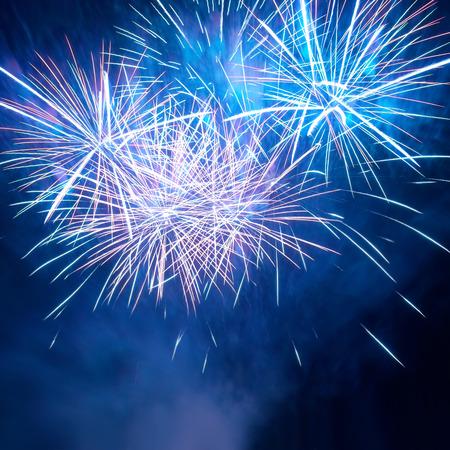 fire works: Blue colorful fireworks on the black sky background. Holiday celebration.