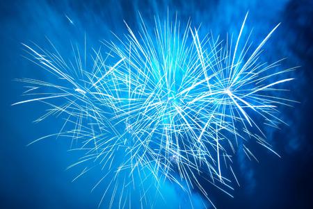 Blue colorful fireworks on the black sky background. Holiday celebration.