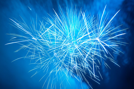 new years eve background: Blue colorful fireworks on the black sky background. Holiday celebration.