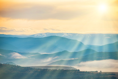 Blue mountains covered with mist against sunset. Bright sun shining on the sky Stock Photo