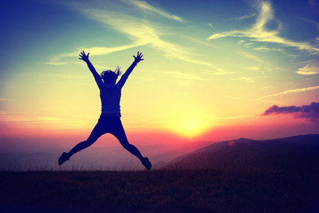 Silhouette of young woman jumping against sunset with blue sky.  photo