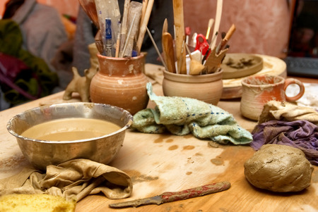 Handmade old clay pots with pencils and other stuff on the table photo