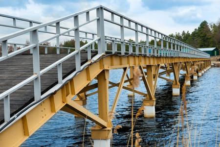 Steel bridge along river bank blue sky at background 版權商用圖片