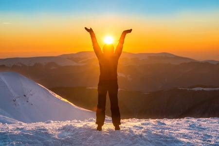 Frau auf der Spitze des Berges im Winter hält Sonne in ihren Händen
