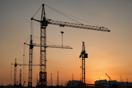 construction machines: Industrial landscape with silhouettes of cranes on the sunset background