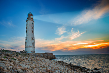 lighthouses: Lighthouse searchlight beam through sea air at night. Seascape at sunset