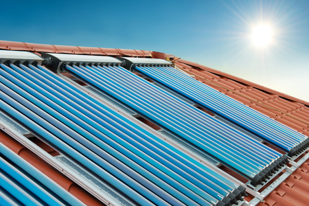 gelio: Vacuum collectors solar water heating system on red roof of the house under shining sun and blue sky