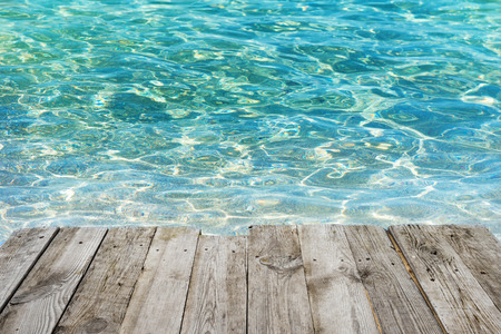 old pier: View from empty wooden deck table to tropical sunny beach with blue water background