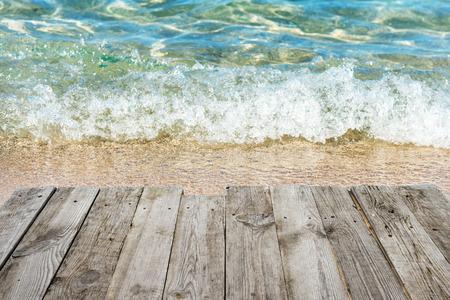 tabla de surf: Vista desde la mesa cubierta de madera vacía a la playa tropical soleado con el surf y fondo azul del agua Foto de archivo