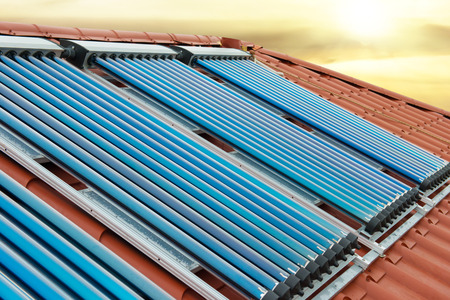 gelio: Vacuum collectors- solar water heating system on red roof of the house under shining sun