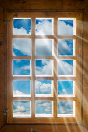 Houten raam met zonnestralen schijnt vanuit prachtig uitzicht op de blauwe lucht en de wolken