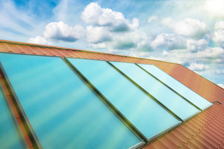 Solar cells on the red house roof under shining sun, blue sky with clouds