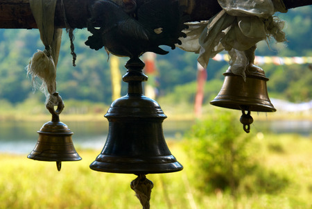 golden temple: Old bronze bells in indian temple in front of shining green lawn Stock Photo