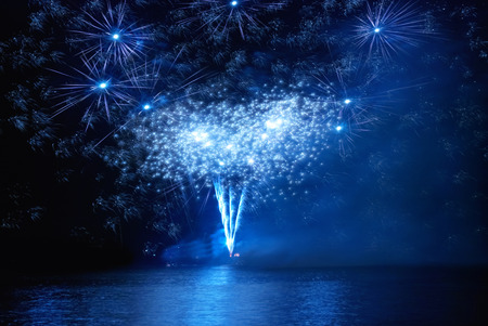 dark green background: Blue holiday fireworks on the black sky background