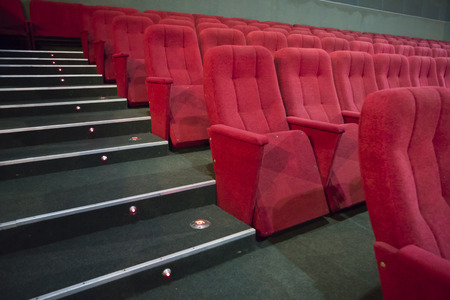 sits on a chair: Aisle with rows of red seats in the modern theater