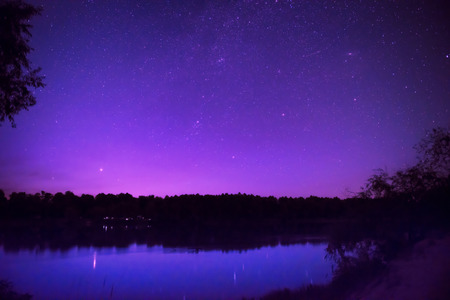 milkyway: Beautiful purple night sky with many stars on a lake with forest on the other coast. Milkyway reflection in water Stock Photo