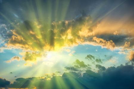 sol: Hermoso cielo azul con el sol brillando a través de nubes