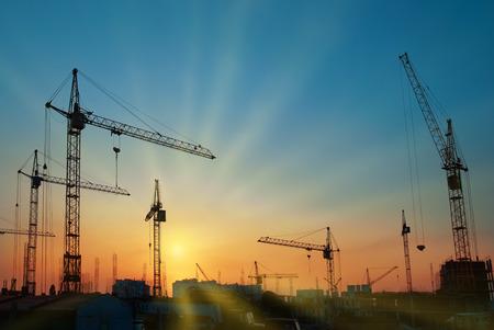 Industrieel landschap met silhouetten van kranen over zonsondergang