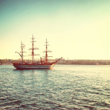 old backgrounds: Beautiful sailing vessel in the sea comes into bay Stock Photo