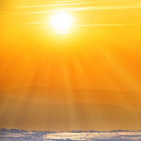 Oranje zonsondergang met grote zon en zonnestralen over de winter bergen Stockfoto