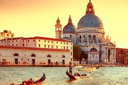 gondoliers: Gondoliers on gondola at Grand Canal in Venice. Basilica Santa Maria della Salute in sunny day.