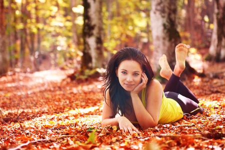 Pretty woman in the autumn forest laying on orange leaves photo