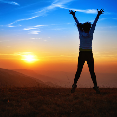 woman sunset: Silhouette of happy young woman jumping against sunset in the mountains