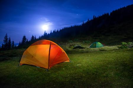 Twee Verlicht oranje en groene camping tenten onder maan, sterren in de nacht