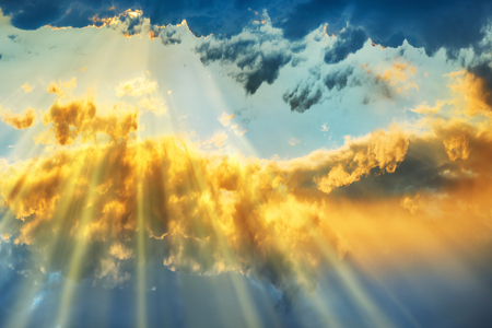 Sunset over beautiful blue sky with sun shining through clouds Banque d'images