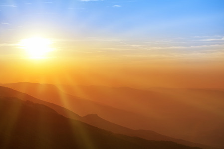 light rays: Beautiful sunset in the mountains. Colorful landscape with sun, sunrays and blue sky