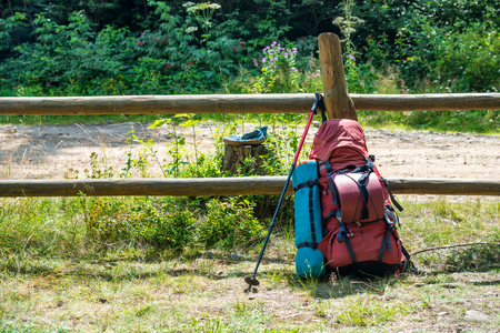 trekking pole: Backpack and trekking pole standing near fence at green grass countryside. Travel outdoor background