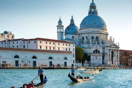 gondoliers: Gondoliers on gondola at Grand Canal in Venice. Basilica Santa Maria della Salute in sunny day Stock Photo