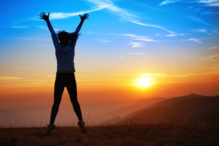 Silhouette of happy young woman jumping against sunset in the mountains photo