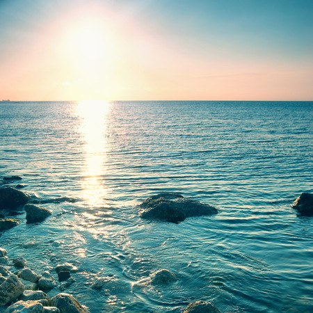 seascape: Sea shore and stones at sunset. Seascape with shining sun
